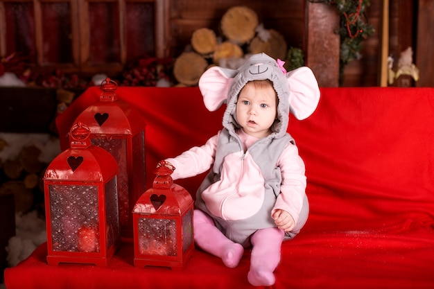Small child (girl) in festive suit of mouse (rat) sits near flashlights and christmas decorations
