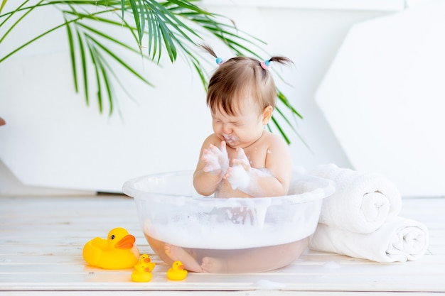 A small child girl got foam in her eyes and mouth in the bath