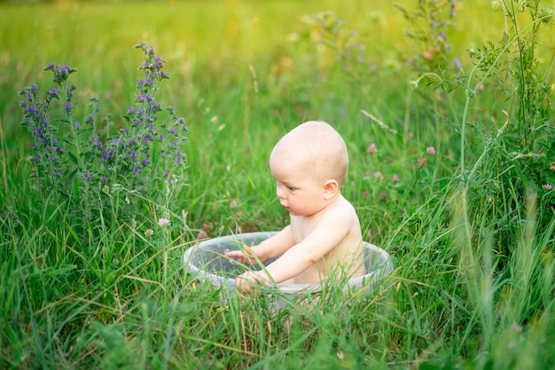 A small child a girl six months old bathes in a basin of foam on a green lawn in the summer