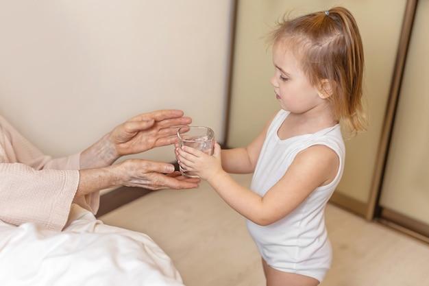Маленький ребенок дает стакан воды бабушке в постели дома