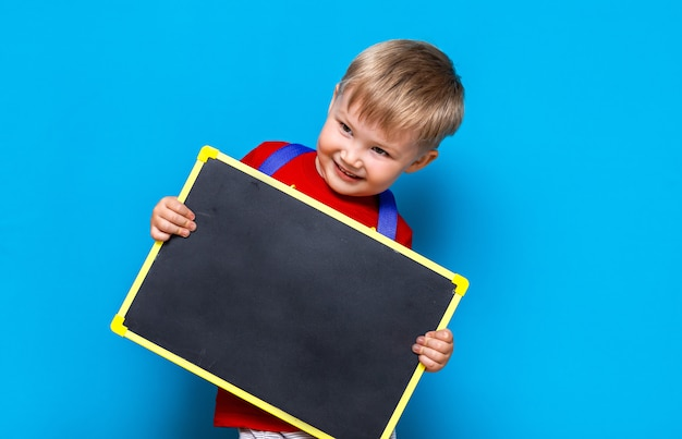 Small child holding chalk blackboard standing