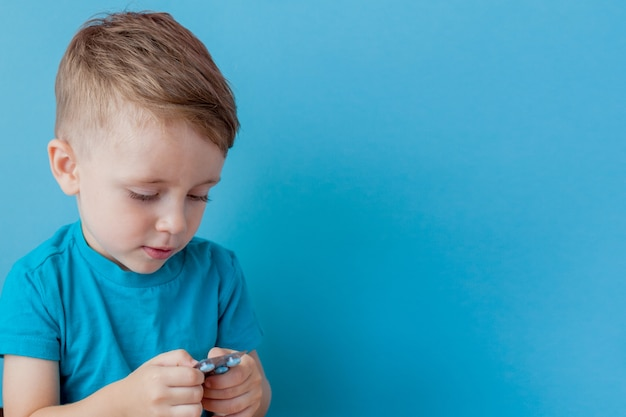 Small child holds in his palm a handful of pills on blue background