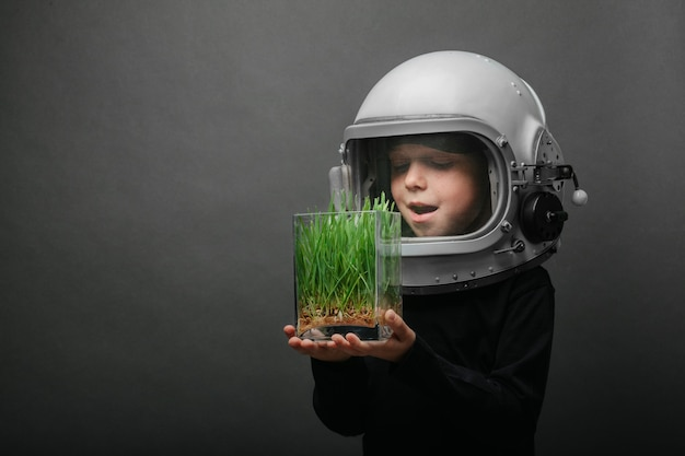 A small child holds plants in an airplane helmet.