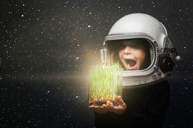 A small child holds plants in an airplane helmet
