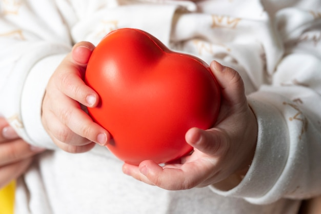 A small child holds a red heart in his hands. concept of maternal love, child health