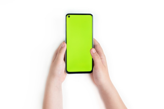 A small child holds a smartphone with a blank green screen in two hands, isolated on a white surface. top view, copy space.