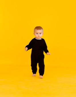 黒のボディースーツを着た小さな子供。彼は黄色いスタジオの背景に微笑んでいます。子供の頃、赤ちゃんの広告に関する記事。スペースをコピーし、クローズアップ