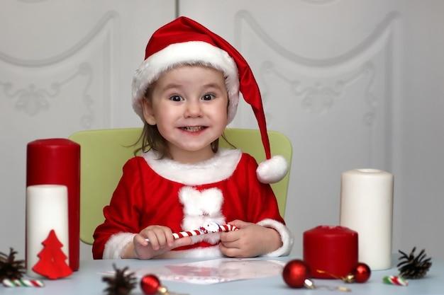 サンタクロースのスーツを着た小さな子供が新年の願いを込めて手紙を書いています