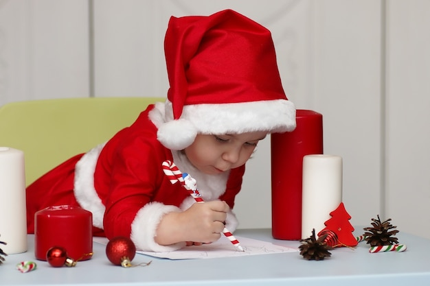 願いを込めて手紙を書くサンタクロースのスーツを着た小さな子供