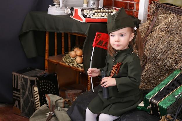 勝利の休日、戦時中の装飾で軍服を着た小さな子供。カントリースタイル。アコーディオン、旗。 5月9日ロシア語の碑文の翻訳:5月9日