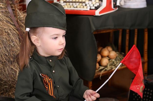 勝利の休日に軍服を着た小さな子供。戦時中の装飾。カントリースタイル。アコーディオン;国旗。 5月9日