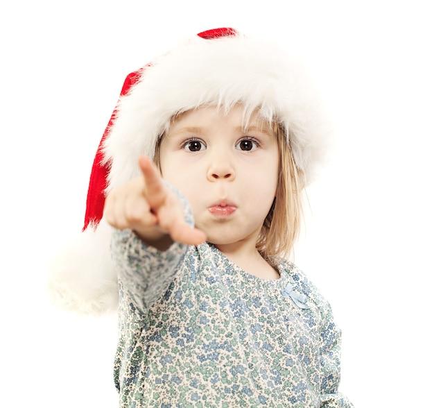 산타 모자에 작은 아이는 흰색에 그녀의 손가락을 가리 킵니다. 나한테 선물 사줬어? 나는 이것을 원한다!