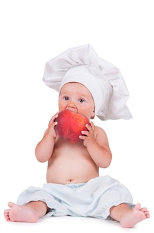 A small child is eating a big peach in a chef suit on a white.