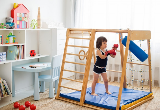 A small child is engaged in boxing on a wooden home sports complex.