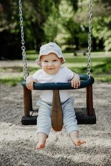 小さな子供はブランコに乗って楽しんでいます
