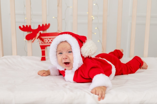 A small child is lying in a santa costume in the crib and crying