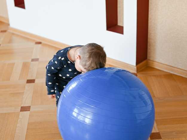 A small child is playing with a ball. baby banging his head on a ball