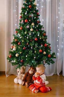Маленькая девочка перекусывает яблоком перед елкой с мягкими игрушками под ним. фото высокого качества
