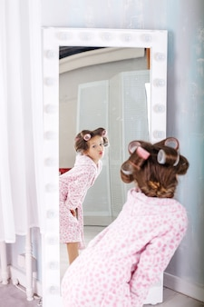A small child looks in the mirror in curlers.