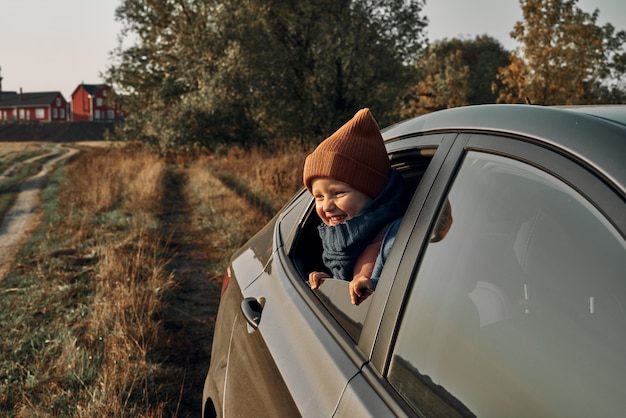 A small child looks out the open car window. lighthouse in the background. traveling with children.