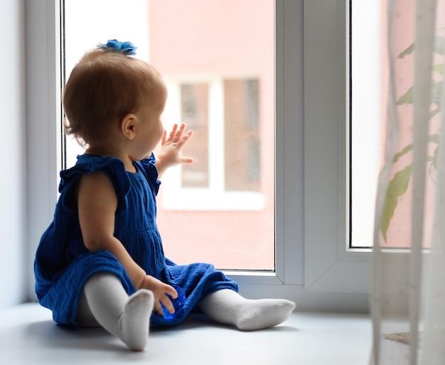 Маленький ребенок смотрит в окно маленькая девочка в платье сидит на окне. оставайся дома изоляция прикоснись к окну ручкой