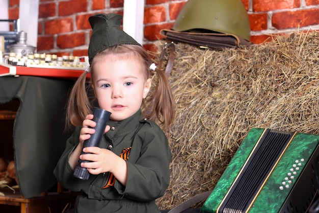 Small child in military uniform on the holiday of victory; wartime decorations. country style.