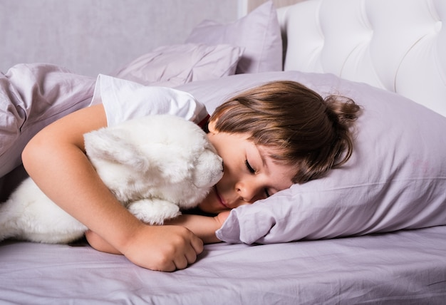 A small child in pajamas sleeps under a blanket on a bed with a white stuffed toy