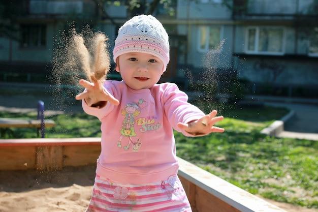뒤뜰과 모래 상자에서 노는 작은 아이