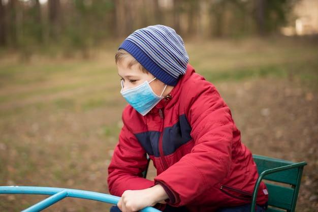 コロナウイルスの流行中に公園の遊び場で遊ぶ小さな子供。ウイルスから保護するための医療用マスクを着ている少年