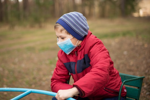 Small child playing on the playground in park during coronavirus epidemic. young boy wearing medical mask for protection from virus