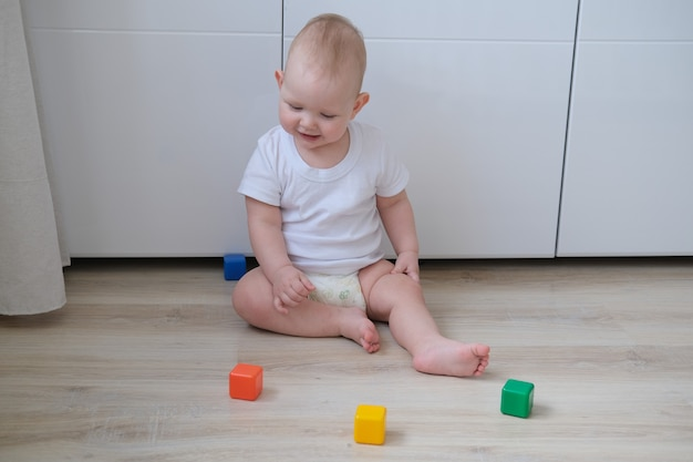 A small child plays on the floor with colored cubes and builds a pyramid out of them.