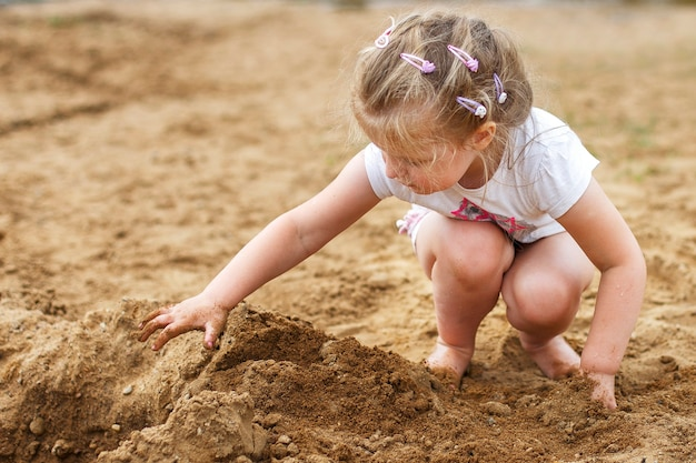 A small child plays with the sand. beautiful girl sitting on the beach.