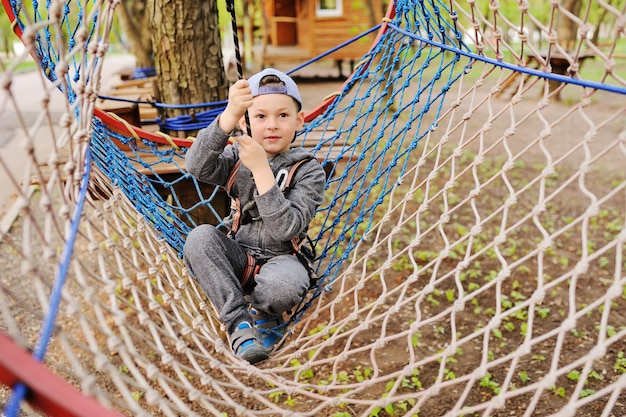 A small child preschooler boy is an obstacle in a safety alpinism equipment high rope park