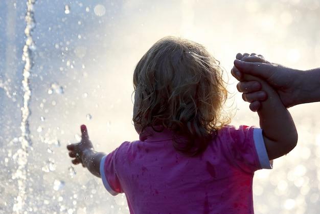 작은 아이가 분수의 물보라에 손을 내밀어