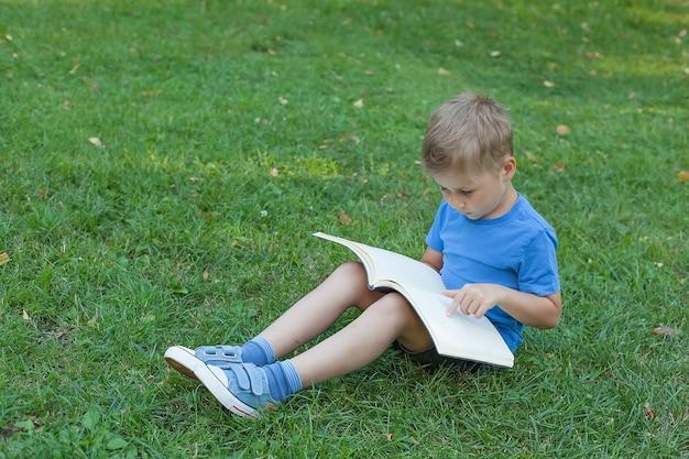 Маленький ребенок читает книгу, лежа на траве.