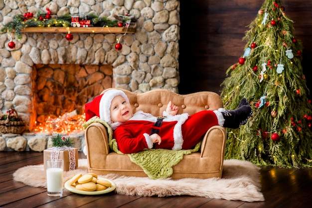 A small child in a red santa claus costume lies on the couch in the residence