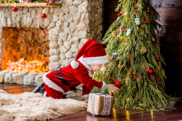 A small child in a red santa claus costume plays by a stone fireplace with bright garlands