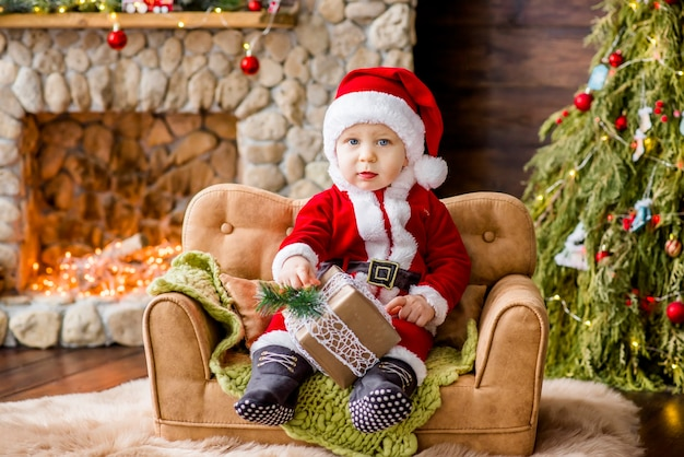 A small child in a red santa claus costume, sitting on the couch in the residence