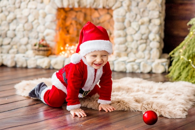 A small child in a red santa claus costume
