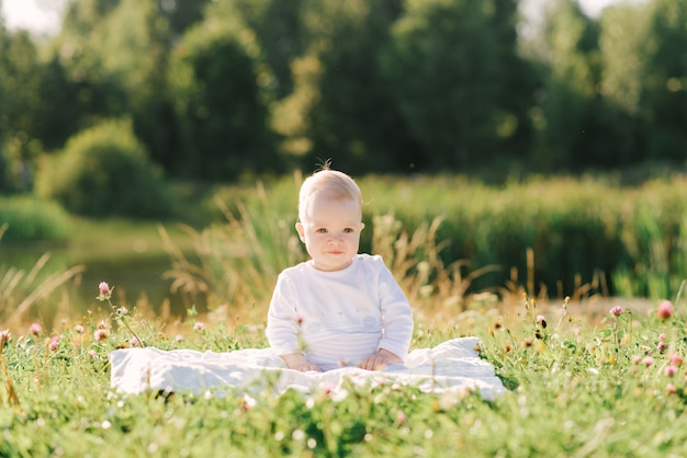 A small child sits on a blanket on the shore of the lake in the open air