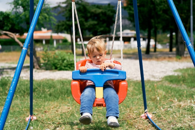 Small child sits on a colorful swing
