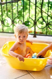 작은 아이는 발코니에 물과 장난감이 있는 분지에 앉아 있다