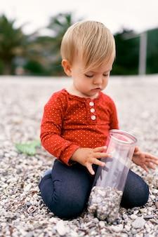 小さな子供は小石のビーチでひざまずいて、小石の瓶を手に持っています