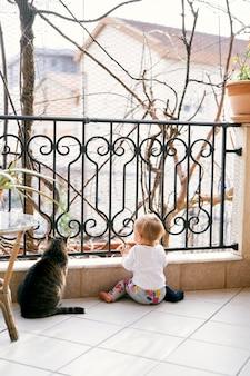 Маленький ребенок сидит на балконе возле кованой решетки и столика с вазонами сидит полосатый кот