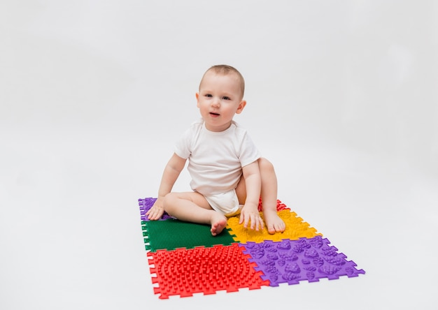 A small child sits on an orthopedic mat