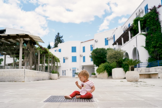 Small child sits on a sewer grate against the background of houses and plants in tubs