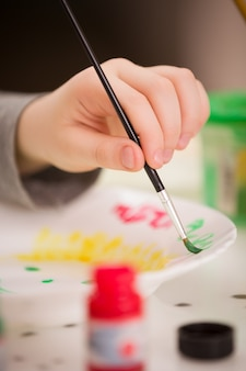 A small child sits at the table and draws with a brush and paints on a plate