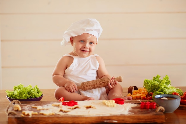 The small child sits on the table near dough and vegetables