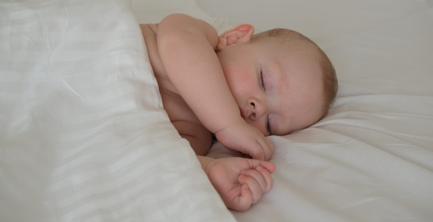 A small child sleeps under a white blanket.
