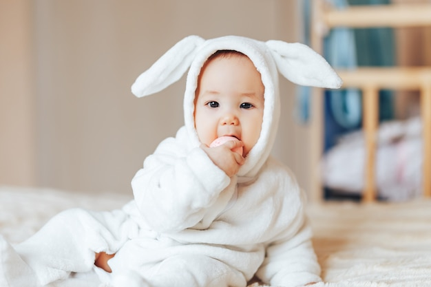 Small child smiling baby in a white bunny rabbit costume easter playing with colourful eggs